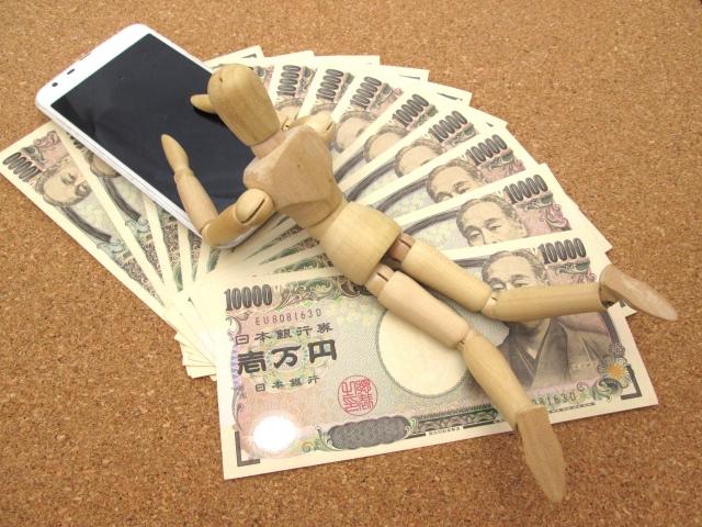 一万円の上で寝そべってスマホを操作する人形
