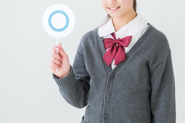 ○の札を持つ女子高生